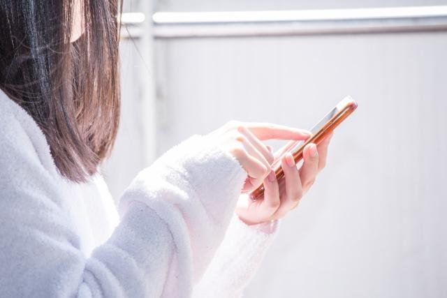 歩きながらスマートフォンを操作する女性